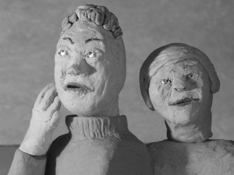 two plasticine heads: foreground one speaking