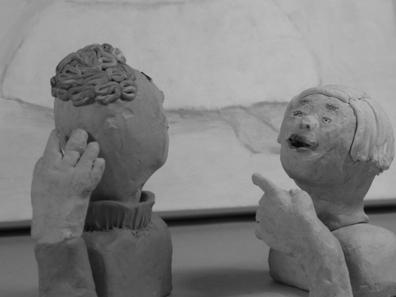 two plasticine heads, one points