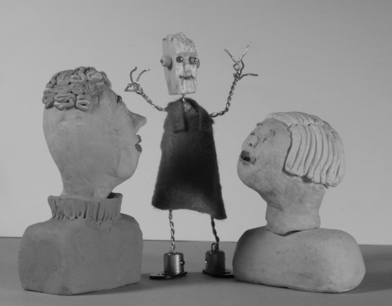 two plasticine heads look at wire model figure