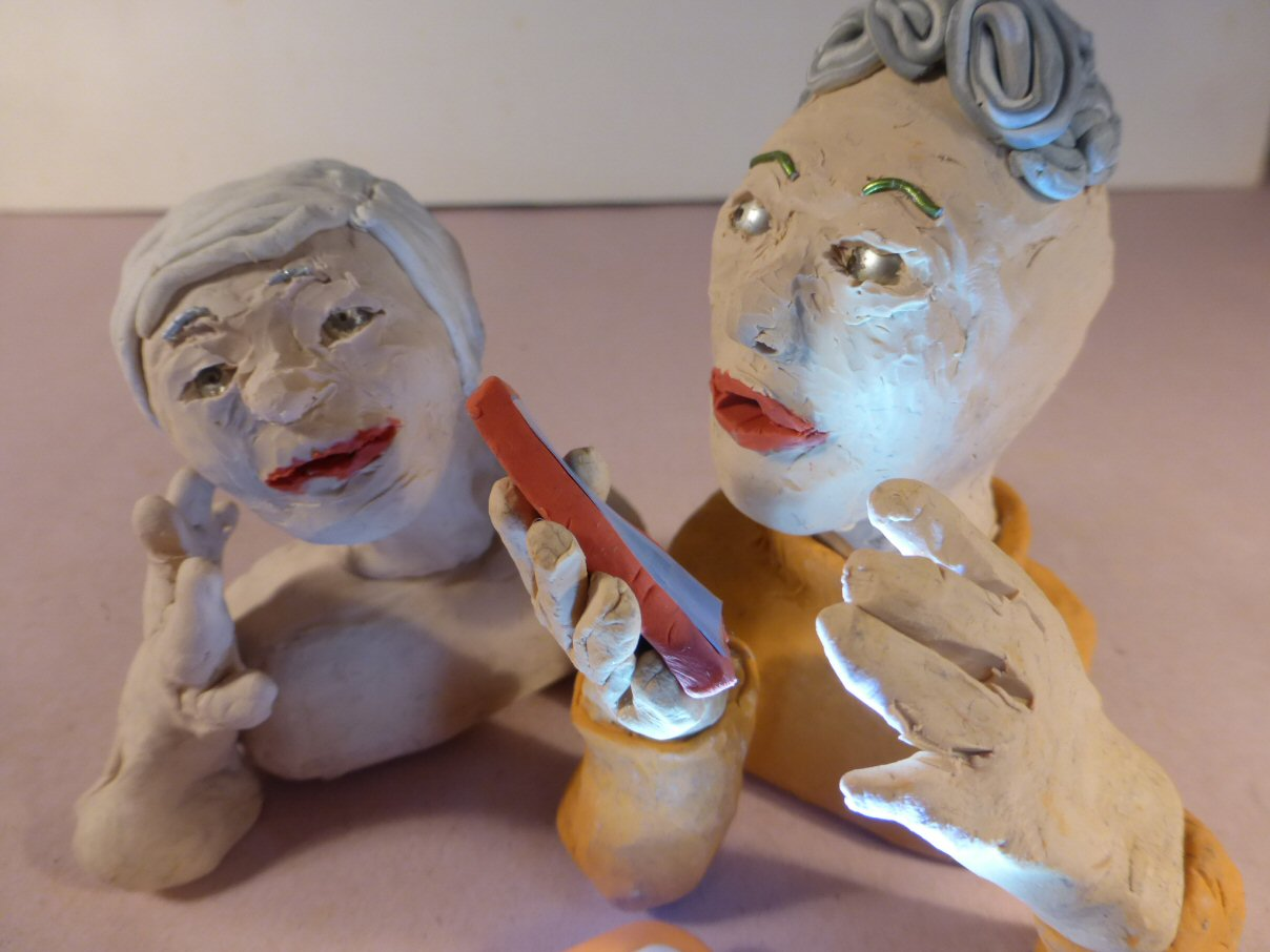 closeup of 2 plasticine heads and smartphone