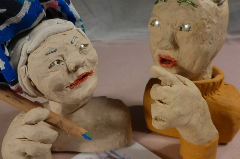 2 plasticine heads with one holding a pencil