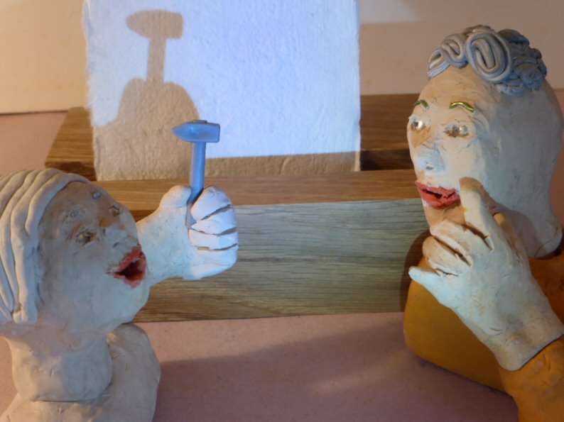 two plasticine heads with hammer and shadow