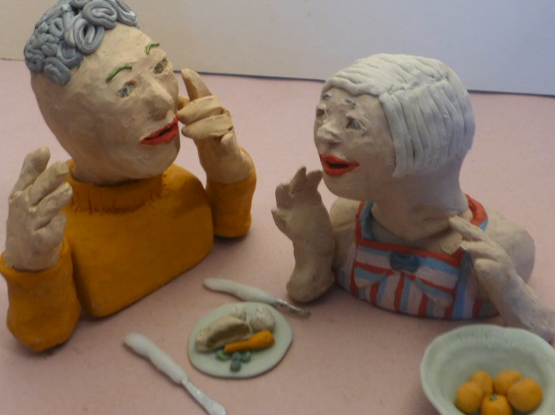 2 plasticine heads and plate of food